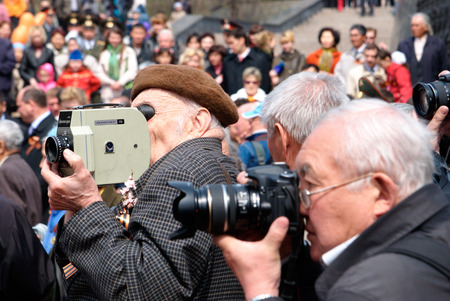 cinematographer: ULAN-UDE, RUSSIA - MAY 9  Unidentified senior reporters - a cinematographer and a photographer shoot on annual Victory Day, May 9 2009 in Ulan-Ude, Buryatia, Russia