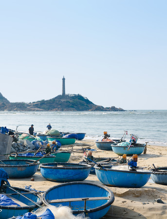 PHAN THIET, VIETNAM - MARCH 6, 2013  Many round boats stay at shore after the night fishing  In the background there is Ke Ga lighthouse, the oldest in Vietnam