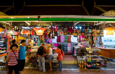 night market: SIEM REAP, CAMBODIA - FEB 21, 2013: Unidentified tourists shop at the night market of Siem Reap. It serves as a gateway to the world famous Angkor temples and is a major tourist hub.