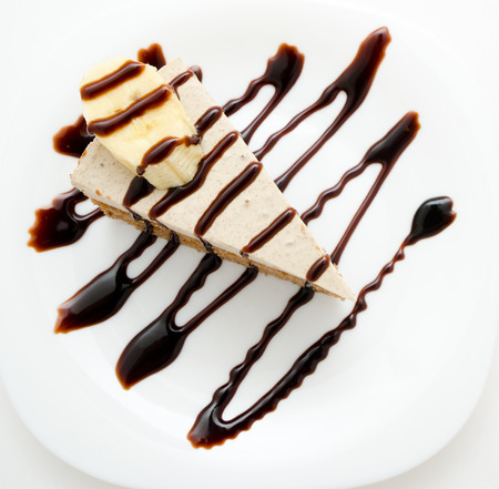 chocolate syrup: fresh cheese cake with chocolate syrup and piece of banana