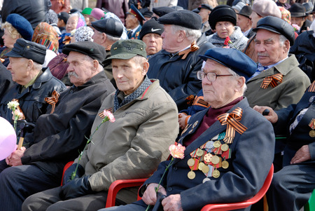 upper half: ULAN-UDE, RUSSIA - MAY 9, 2008: Elderly veterans of WWII sit at tribunes and watch the parade on annual Victory Day.