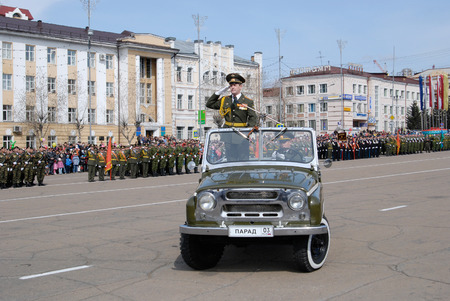 ULAN-UDE, RUSSIA - MAY 9, 2010: The commander standing in a car salute to officers - participants of the parade on annual Victory Day.