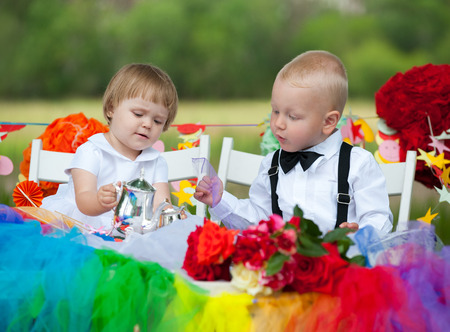 baby girl and boy sit at festive table photo