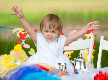 baby girl sits at festive table, spreading her arms photo