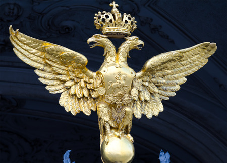double headed: ST  PETERSBURG - JUNE 30, 2011  One of three golden double headed eagles at forged gate at Southern facade of the Winter Palace  From 1732 to 1917 it was the official residence of Russian monarchs  Editorial