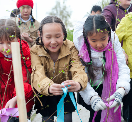 ulan ude: ULAN-UDE, RUSSIA - MAY 20, 2011  Unidentified children tie up ribbons on young trees they have just planted near the City Palace of Childrens Arts which they attend