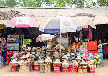 tradeswomen: ANGKOR, CAMBODIA - FEB 21, 2013  Unidentified tradeswomen sell various hats at a little market  The Angkor Khmer complex is the prime tourists attraction in the country  Editorial