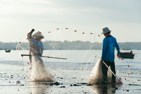 MUI NE, VIETNAM - FEBRUARY 27, 2013  Two unidentified Vietnamese fishers fold a net at the shore  Fishing is one of the principal sources of income for local people