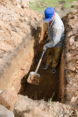 ocas: Hombre de raza blanca en la gorra azul cava la tumba en el cementerio
