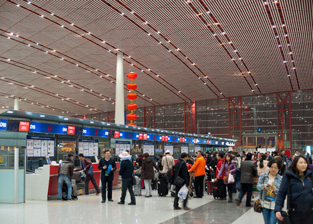BEIJING - FEB 16, 2013  A lot of passengers stand in queues to check in counters at Beijing International airport  In 2014 it is the busiest airport in the world in terms of passenger throughput