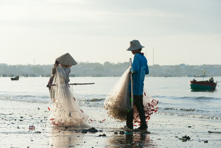 MUI NE, VIETNAM - FEBRUARY 27, 2013  Two unidentified Vietnamese fishers  a woman and a man  fold a net at the shore  Fishing is one of the principal sources of income for local people