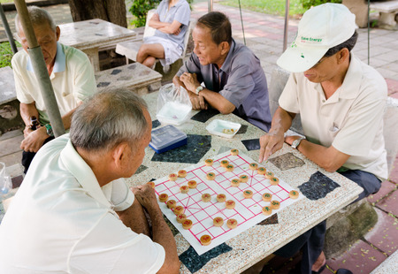 BANGKOK, THAILAND - FEB 17, 2013  Unidentified local senior men spend spare time playing Chinese chess in the street