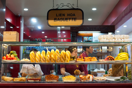 DALAT, VIETNAM - JUNE 6, 2014: Unidentified bakery worker stuffs a baguette with some filling. It depends on clients choice. Very popular fast food service.
