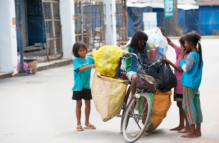 SIEM REAP, CAMBODIA - JUNE 28, 2014: Four local unidentified girls of school age arrange large bags with different kinds of trash on a bicycle. In Khmer family every member must earn money.