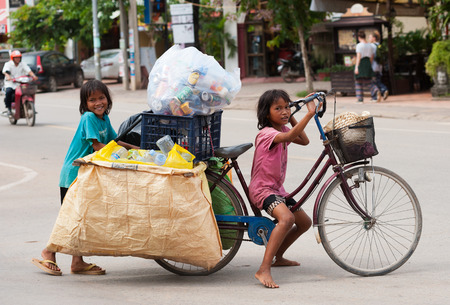 SIEM REAP, CAMBODIA - JUNE 28, 2014: Two local unidentified girls of school age pose for camera carrying large bags with trash on a bicycle. In Khmer family every member must earn money.