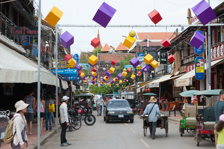 SIEM REAP, CAMBODIA - JUNE 28, 2014: Unidentified tourists and locals stroll along Pub Street. It is famous with plenty of restaurants and located in the heart of the tourist area.