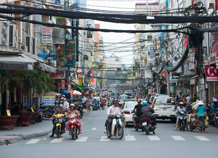 lao: HO CHI MINH, VIETNAM - JULY 7, 2014: Unidentified local people and tourists walk and drive along Bui Vien Street. It is in Pham Ngu Lao area popular among backpackers. Editorial