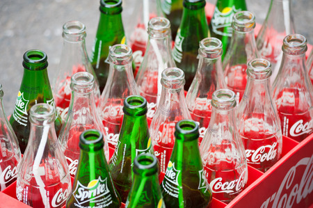 HO CHI MINH, VIETNAM - JULY 7, 2014: Empty bottles of Coca Cola and Sprite in a plastic box. Based on Interbrands best global brand study of 2011, Coca-Cola was the worlds most valuable brand.