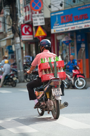 interbrand: HO CHI MINH, VIETNAM - JULY 7, 2014: An unidentified delivery man rides a motor bike carrying a box with empty bottles of coca cola and sprite. Based on Interbrand best global brand study of 2011, Coca-Cola was the worlds most valuable brand.