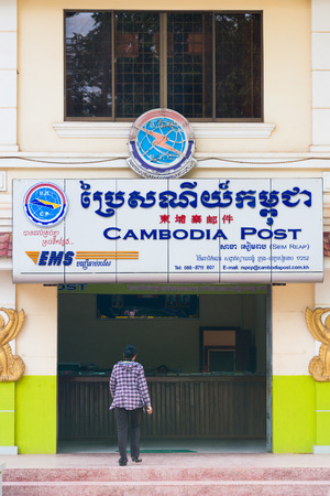 siem reap: SIEM REAP, CAMBODIA - JUNE 28, 2014: An unidentified woman enters a post office in the downtown. The national postal service offers a wide range of services though in general things go slowly.