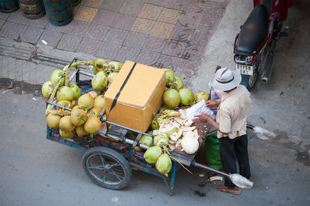 penh: PHNOM PENH, CAMBODIA - JULY 3, 2014: An unidentified man selling coconuts from his cart unfolds a packet to put a peeled coconut into it.