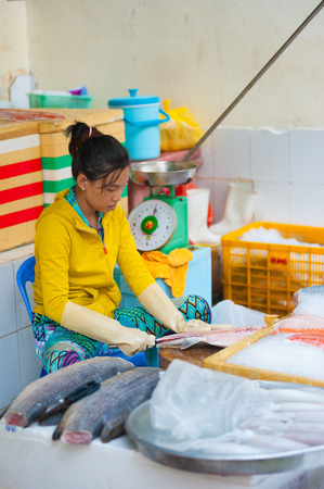 half fish: HO CHI MINH, VIETNAM - JULY 5, 2014:  An unidentified young woman at Ben Thanh market cuts a fresh salmon for sale. While tourists search here souvenirs townspeople come to buy fresh food.