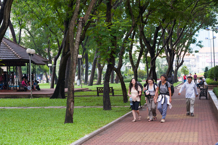lao: HO CHI MINH, VIETNAM - JULY 5, 2014: Unidentified young women tourists carrying rucksacks walk in the park in Pham Ngu Lao Street. The area near the street is popular among backpackers.