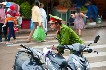 possession: DALAT, VIETNAM - JULY 23, 2014: An unidentified policeman checks documents on right of possession of vehicles. Editorial
