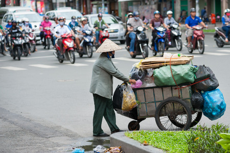 sorted: HO CHI MINH, VIETNAM - JULY 6, 2014:  An unidentified senior dustwoman rolls a cart with different kinds of sorted waste for recycling. Waste selling for recycling is popular business in Vietnam.