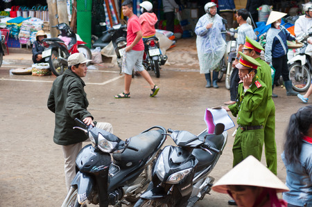 possession: DALAT, VIETNAM - JULY 23, 2014: Two unidentified policemen check documents on right of possession of vehicles at a market parking lot.