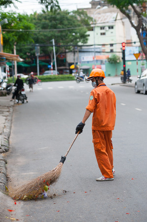 sweeper: HO CHI MINH, VIETNAM - JULY 6, 2014: An unidentified street sweeper in an orange uniform sweeps a road in the downtown.
