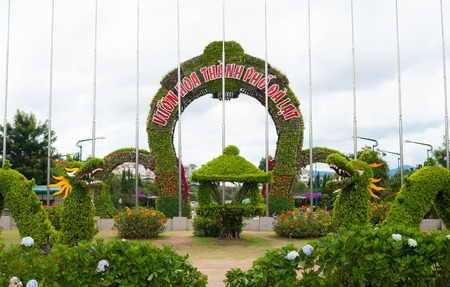 settled: DALAT, VIETNAM - JULY 17, 2014: The main entrance of the Flower Park, one of major tourist attrations in the city. The arch consists of lots of flowers in pots settled on a metal frame.
