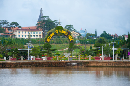 settled: DALAT, VIETNAM - JULY 24, 2014: The main entrance of the Flower Park, one of major tourist attrations in the city. The arch consists of lots of flowers in pots settled on a metal frame.
