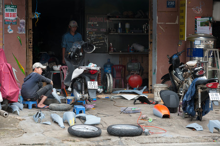 motorcycle repair shop: DALAT, VIETNAM - JULY 25, 2014: An unidentified teenager cleans a spare part of a motorcycle at a repair shop. Editorial
