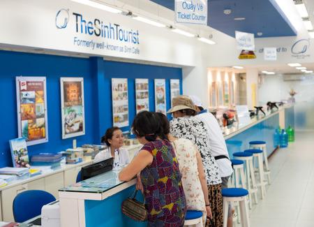 agencia de viajes: HO CHI MINH, Vietnam - 15 de julio 2014: La gente no identificada de pie en el mostrador de la Sinh turística. De acuerdo con muchos de los comentarios de la compañía parece ser la agencia tour más popular y de buena reputación de Vietnam.