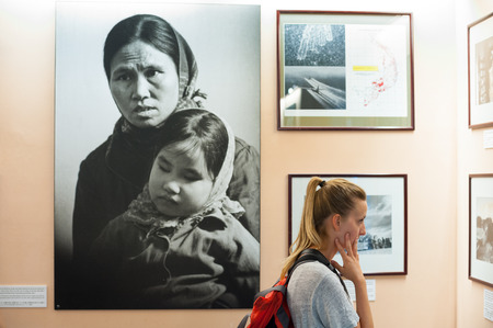 startled: HO CHI MINH, VIETNAM - JULY 15, 2014: A Caucasian woman watches photographs at the War Remnants Museum. It primarily contains exhibits relating to the American phase of the Vietnam War.
