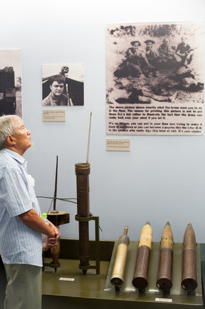 remnants: HO CHI MINH, VIETNAM - JULY 15, 2014: An Asian senior man presumptively a Vietnamese watches photographs at the War Remnants Museum.