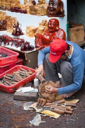 carver: Dalat, Vietnam - 28 de julio 2014: Un tallador no identificado talla una estatuilla de madera.