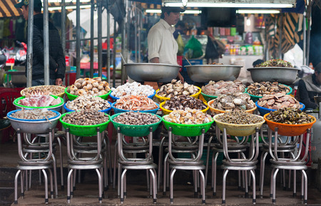 local 27: DALAT, VIETNAM - JULY 27, 2014: An unidentified man sells and cooks different kinds of seashells and seafood at a local food market. Editorial