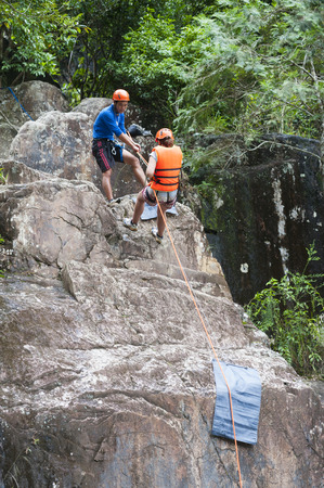 abseil: DALAT, VIETNAM - JULY 28, 2014: An unidentified Caucasian young woman tourist rappels in Datanla waterfall with the help of a local guide.