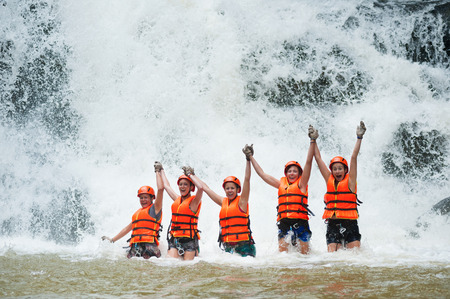rappel: DALAT, VIETNAM - JULY 28, 2014: Unidentified Caucasian young women tourists having abseiled in Datanla waterfall pose for camera smiling happily with arms spread.
