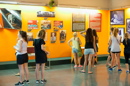 places of interest: HO CHI MINH, VIETNAM - JULY 15, 2014: Unidentified tourists watch photographs at the War Remnants Museum relating to Agent Orange. This herbicide was used by the U.S. military during the Vietnam War.