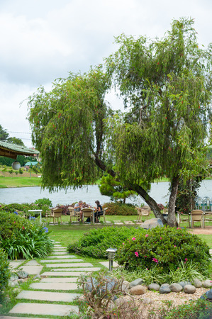 cau: DALAT, VIETNAM - JULY 17, 2014: A couple of unidentified Caucasian tourists have lunch at a cafe in the Bich Cau Garden. It is located on a small island in the northern part of Xuan Huong Lake. Editorial