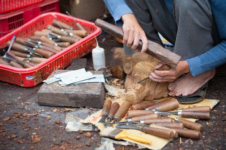 tallado en madera: Dalat, Vietnam - 28 de julio 2014: Un tallador no identificado talla una estatuilla de madera.