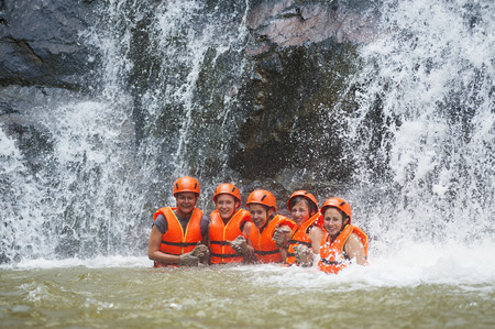rappel: DALAT, VIETNAM - JULY 28, 2014: Unidentified Caucasian young women tourists having abseiled in Datanla waterfall pose for camera smiling happily and holding each other.