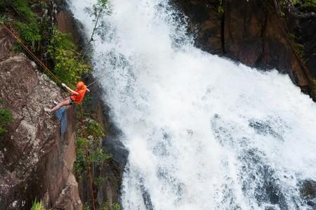 abseil: DALAT, VIETNAM - JULY 28, 2014: An unidentified Caucasian young woman tourist rappels in Datanla waterfall.