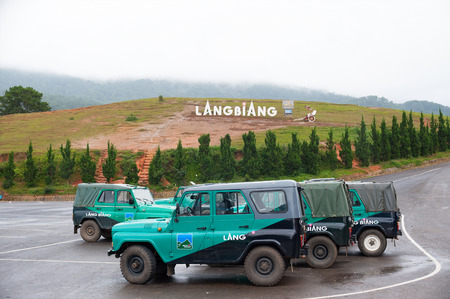 lang: DALAT, VIETNAM - JULY 30, 2014: A parking lot with off road vehicles at the foot of Lang Biang mountain. Its height is 1,900m and one can walk there by a 3 hours hike, or can ride by a jeep. Editorial
