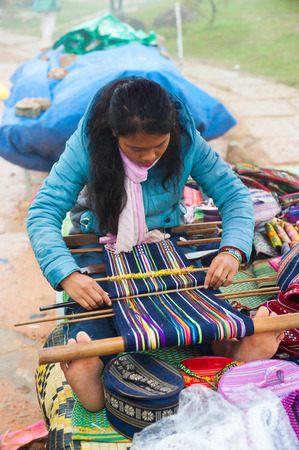 lang: DALAT, VIETNAM - JULY 30, 2014: An unidentified local young woman weaves by hand at Lang Biang mountain. Its height is 1,900m and one can walk there by a 3 hours hike, or can ride by a jeep.