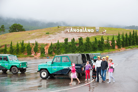 lang: DALAT, VIETNAM - JULY 30, 2014: Unidentified people walk at the foot of Lang Biang mountain. Its height is 1,900m and one can walk there by a 3 hours hike, or can ride by a jeep.