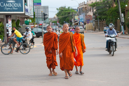 practiced: SIEM REAP, CAMBODIA - JUNE 28, 2014: Three unidentified young Buddhist monks walk in the downtown. Theravada Buddhism is the official religion of Cambodia, practiced by 95 percent of the population.